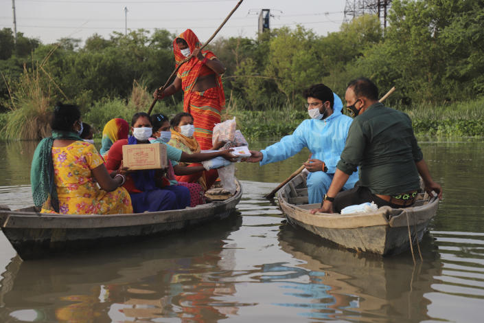 Indian man Himanshu, wearing personal protective suit as a precaution against the coronavirus distributes free aid procured by him to people living in a small island in River Yamuna in New Delhi, India, Wednesday, June 2, 2021. (AP Photo/Amit Sharma)