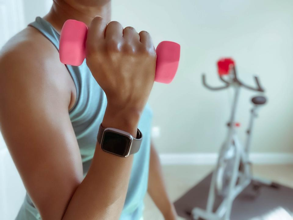 Close-up of unrecognizable black woman holding lightweight dumbbell after indoor cycling session