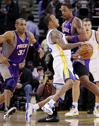 Golden State Warriors' Monta Ellis, center, drives against Phoenix Suns' Channing Frye and Grant Hill (33) during the first half of an NBA basketball game, Monday, Feb. 13, 2012, in Oakland, Calif. (AP Photo/Ben Margot)