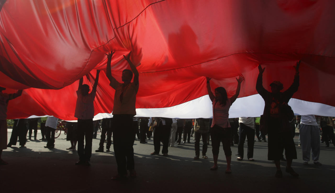 Indonesian activists hold up a huge Indonesian flag during a rally to mark the 10th anniversary of the 9/11 terrorists attacks on the United States, in Jakarta, Indonesia, Sunday, Sept. 11, 2011. (AP Photo/Achmad Ibrahim)