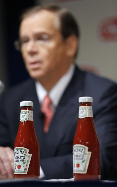 H.J. Heinz Co. CEO William Johnson, is seen behind two bottles of Heinz ketchup as he speaks at a news conference at the world headquarters of the H.J. Heinz Co. on Thursday, Feb. 14, 2013, in Pittsburgh. Billionaire investor Warren Buffett's Berkshire Hathaway and its partner on the deal. 3G Capital, are dipping into the ketchup business as part of a $23.3 billion deal to buy the Heinz ketchup company. (AP Photo/Keith Srakocic)