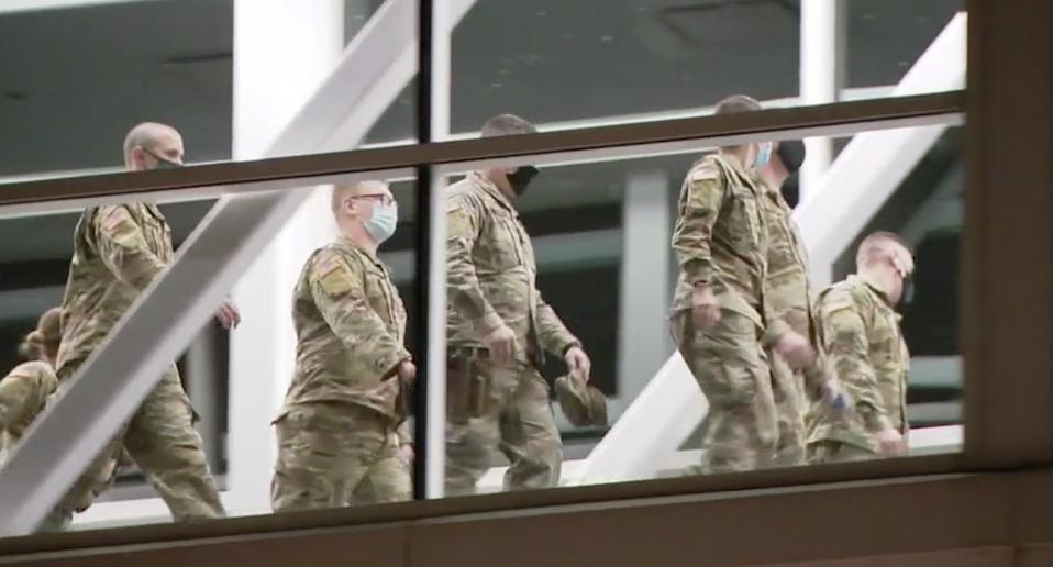 National Guard troops walk past a window after arriving in Chicago ahead of the US election.