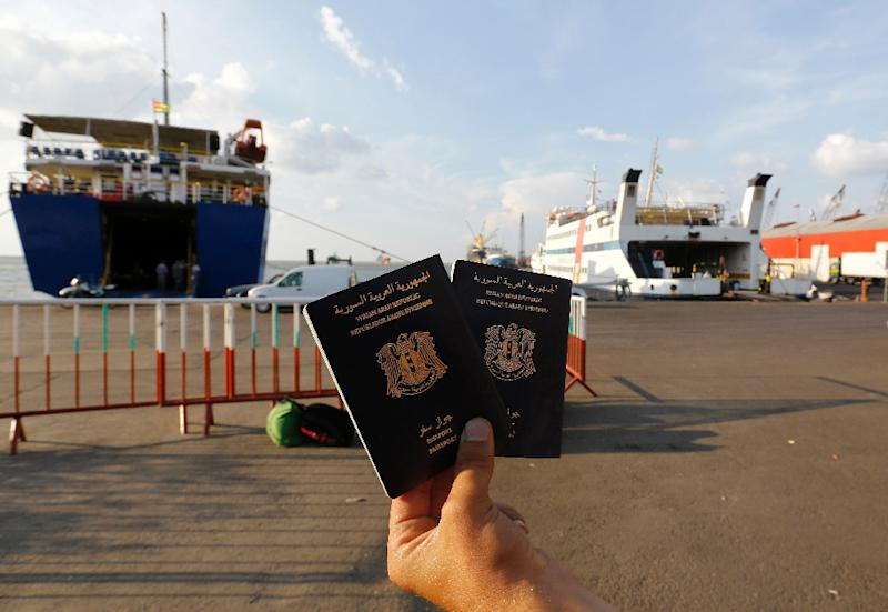 A Syrian man holds Syrian passports as he waits to board a passenger ferry heading to Turkey at Lebanon's northern port city of Tripoli on October 6, 2015