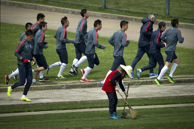 In this Thursday, April 9, 2015 photo, members of the Shanghai Shenhua soccer squad jog past a groundskeeper as they warm up during practice at the team's training facility in Shanghai. While a few years ago Chinese Super League (CSL) soccer was mired in corruption scandals and poor play, Shenhua is emblematic of the new and improved CSL - it's increasingly globalized, brimming with newfound professionalism and flush with cash. (AP Photo/Mark Schiefelbein)