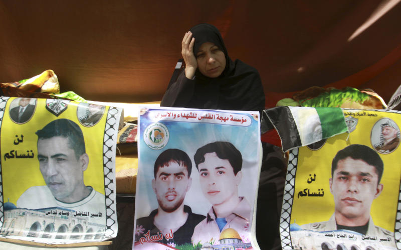 """A Palestinian woman participates in a demonstration in Gaza City in solidarity with prisoners jailed in Israel, Monday, May 7, 2012. According to Israel's Prison Service at least one-third of the 4,600 Palestinian prisoners in Israel began a collective hunger strike in mid-April 2012. The Arabic on the posters reads """"we will not forget you."""" (AP Photo/Hatem Moussa)"""