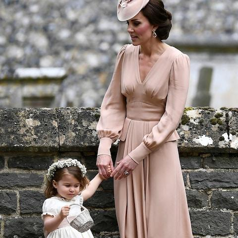 The Duchess of Cambridge holds Princess Charlotte's hand at the wedding of her sister Pippa Middleton - Credit: Justin Tallis/AFP