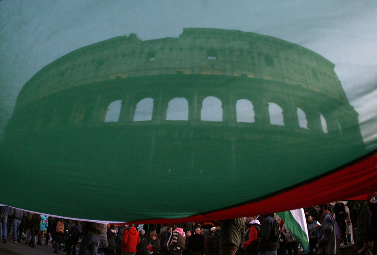 Protesters hold a large Palestinian flag in front of the Colosseum during a protest against Israel's attacks on Gaza, in Rome January 17, 2009.  REUTERS/Alessia Pierdomenico