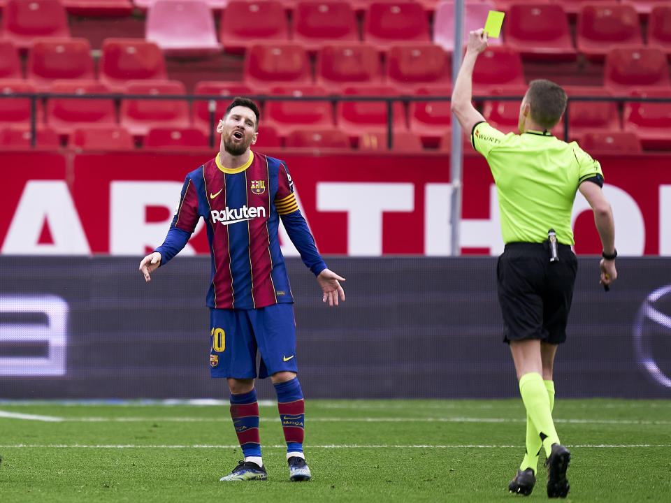 SEVILLE, SPAIN - FEBRUARY 27: A yellow card is shown to Lionel Messi of FC Barcelona during the La Liga Santander match between Sevilla FC and FC Barcelona at Estadio Ramon Sanchez Pizjuan on February 27, 2021 in Seville, Spain. Sporting stadiums around Spain remain under strict restrictions due to the Coronavirus Pandemic as Government social distancing laws prohibit fans inside venues resulting in games being played behind closed doors. (Photo by Mateo Villalba/Quality Sport Images/Getty Images)