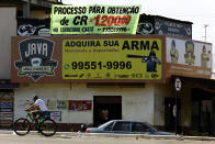 """Advertisments promote the sales of armed weapons with one banner reading in Portuguese: """"Get your weapon here,"""" in Luziania, Brazil, Thursday, March 4, 2021. Brazilian President Jair Bolsonaro is pushing to deliver on his promise to arm every person that wants it. (AP Photo/Eraldo Peres)"""