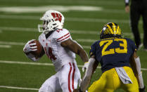 Wisconsin running back Nakia Watson (14) rushes past Michigan linebacker Michael Barrett (23) in the first quarter of an NCAA college football game in Ann Arbor, Mich., Saturday, Nov. 14, 2020. (AP Photo/Tony Ding)
