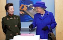 <p>Princess Anne and her mother, the Queen, cut a white cake with a pink sign celebrating International Women's Day. </p>