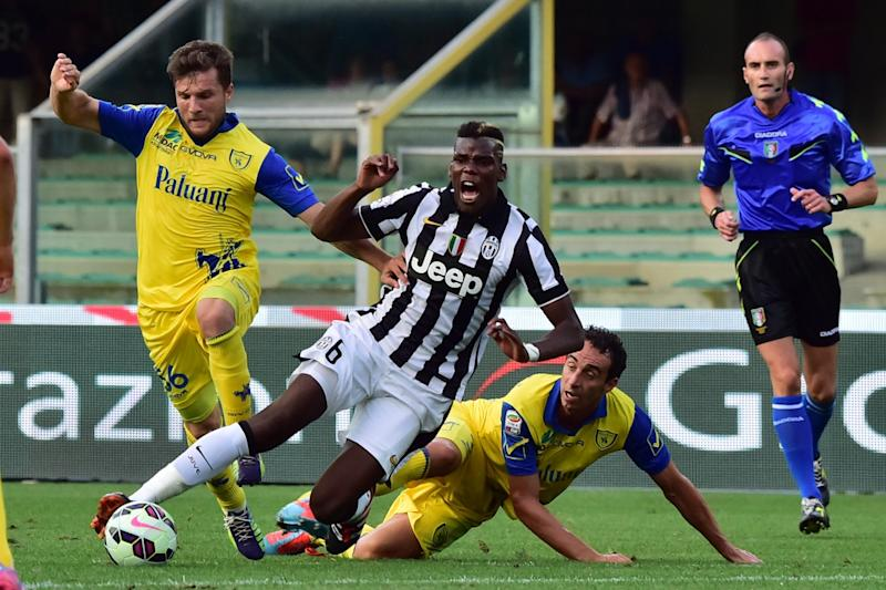 Juventus french midfielder Paul Labile Pogba is tackled by ChievoVerona's Argentine midfielder Mariano Izco during the Serie A football match Chievo Verona vs Juventus at Bentegodi Stadium in Verona on August 30, 2014