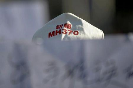 FILE PHOTO: A family member of a passenger onboard Malaysia Airlines flight MH370 holds a banner during a gathering in front of the Malaysian Embassy in Beijing