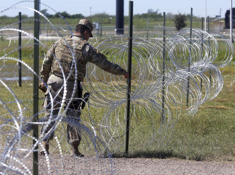 Members of the military police close a barbed wire entrance to Base Camp Donna as U.S. Secretary of Defense James Mattis visits on Wednesday, Nov. 14, 2018, in Donna, Texas. (Joel Martinez/The Monitor via AP)