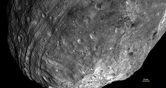Vesta used to be round—until it got hit by something nearly one-tenth its size. The resulting impact basin, named Rheasilvia, fills most of this image, taken from some 5,200 kilometers away. Vesta's south pole lies in the mountains at lower rig