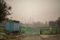 A security guard stands behind a mesh screen at a construction site enveloped in smog and dust in New Delhi, India, Wednesday, Nov. 4, 2020. A thick quilt of smog lingered over the Indian capital and its suburbs on Friday, fed by smoke from raging agricultural fires that health experts worry could worsen the city's fight against the coronavirus. Air pollution in parts of New Delhi have climbed to levels around nine times what the World Health Organization considers safe, turning grey winter skies into a putrid yellow and shrouding national monuments. (AP Photo/Altaf Qadri)