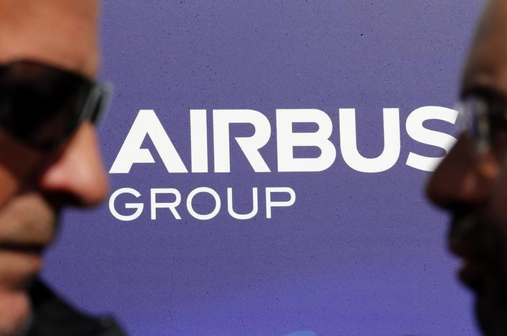 Visitors walk past the logo of Airbus Group during the e-Aircraft Day at the Bordeaux Merignac airport