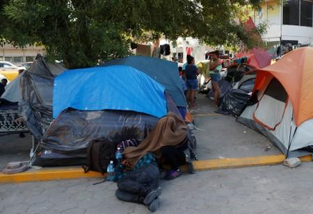 Central American migrants rest outside their tents in an encampment in Matamoros