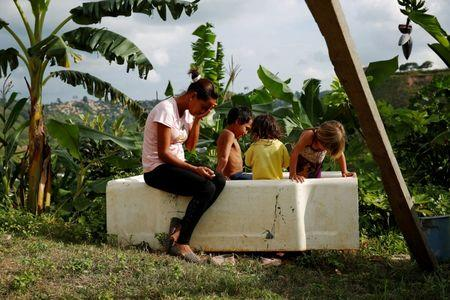 Lisibeht Martinez (L), 30, who was sterilized one year ago, sits next to her children while they play in a bathtub in the backyard of their house in Los Teques, Venezuela July 19, 2016. REUTERS/Carlos Garcia Rawlins