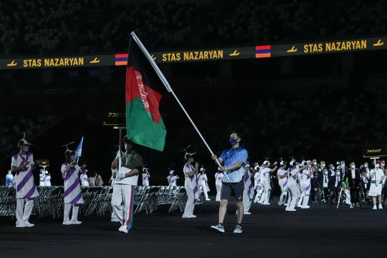 The Afghan flag was carried by a volunteer at the Paralympic opening ceremony (AFP/YASUYOSHI CHIBA)