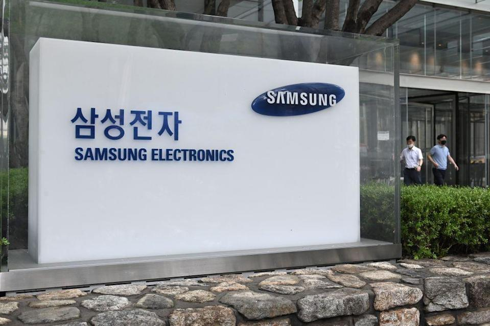 People walk past the logo of Samsung Electronics at the company's Seocho building in Seoul on July 30, 2020. - Samsung Electronics reported on July 30 its net profit grew 7.3 percent year-on-year in the second quarter, with strong demand for memory chips overcoming the impact of the coronavirus pandemic on smartphone sales. (Photo by Jung Yeon-je / AFP) (Photo by JUNG YEON-JE/AFP via Getty Images)
