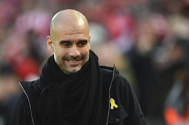 Charged: Pep Guardiola sporting the yellow ribbon (AFP Photo/Oli SCARFF )