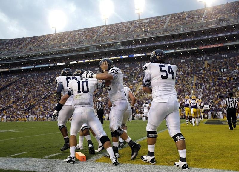 Kent State quarterback Colin Reardon (10) celebrates his touchdown carry with offensive linesman Reno Reda (55) and offensive linesman Jason Bitsko (54) in the first half of an NCAA college football game against LSU in Baton Rouge, La., Saturday, Sept. 14, 2013