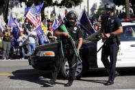 Police officers hold weapons in front of a crowd of President Donald Trump supporters outside of City Hall Wednesday, Jan. 6, 2021, in Los Angeles. Demonstrators supporting President Trump are gathering in various parts of Southern California as Congress debates to affirm President-elect Joe Biden's electoral college victory. (AP Photo/Marcio Jose Sanchez)