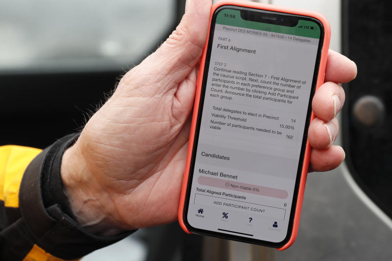 Precinct captain Carl Voss, of Des Moines, Iowa, holds his iPhone that shows the Iowa Democratic Party's caucus reporting app, Tuesday, Feb. 4, 2020, in Des Moines, Iowa. (AP Photo/Charlie Neibergall)