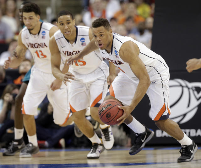 Virginia guard Justin Anderson (1) moves the ball as Anthony Gill (13) and Malcolm Brogdon (15) look on during the second half of an NCAA college basketball second-round tournament game against Coastal Carolina, Friday, March 21, 2014, in Raleigh. (AP Photo/Chuck Burton)