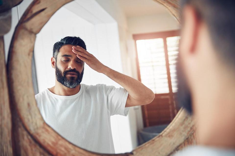 Shot of a man standing in front of the bathroom mirror looking exhausted, holding his head