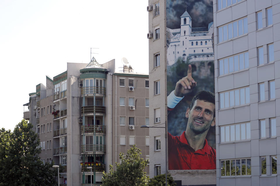 A billboard depicting Serbian tennis player Novak Djokovic and the Christian Orthodox monastery of Ostrog is seen on a building in Belgrade, Serbia, Wednesday, June 24, 2020. Djokovic has tested positive for the coronavirus after taking part in a tennis exhibition series he organized in Serbia and Croatia. The top-ranked Serb is the fourth player to test positive for the virus after first playing in Belgrade and then again last weekend in Zadar, Croatia.(AP Photo/Darko Vojinovic)