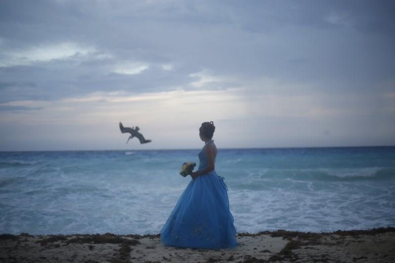 <p>Some spots still appear picturesque. Here, a girl looks at a bird fishing in the sea in Cancun October 14, 2015.<i> (Photo: Reuters/Edgard Garrido)</i><br></p>
