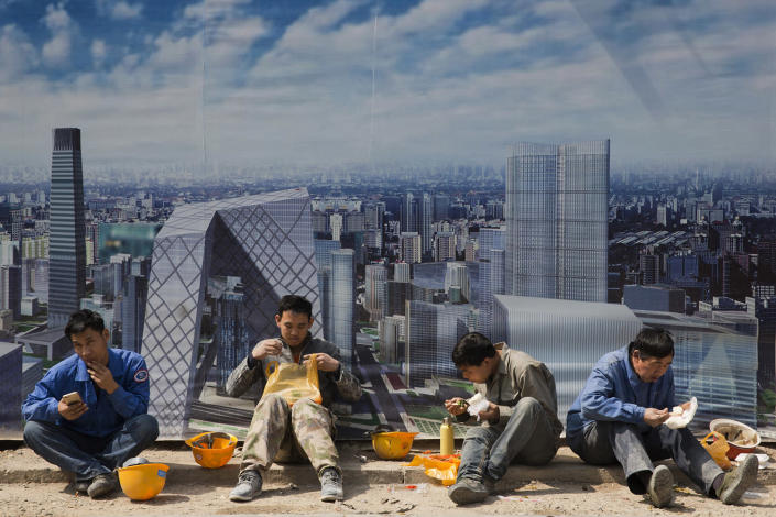 <p>Construction workers eat lunch near a board with an artist's impression of the Central Business District outside a construction site in Beijing, China, April 6, 2017. Asia's developing economies will see steady growth this year and the next, though the evolving policies of President Donald Trump's administration are a major uncertainty, the Asian Development Bank said in a report Thursday. It said 30 of the 45 countries covered in the report will see sustained growth that will help offset the gradual slowdown in China, Asia's biggest economy. (Photo: Ng Han Guan/AP) </p>