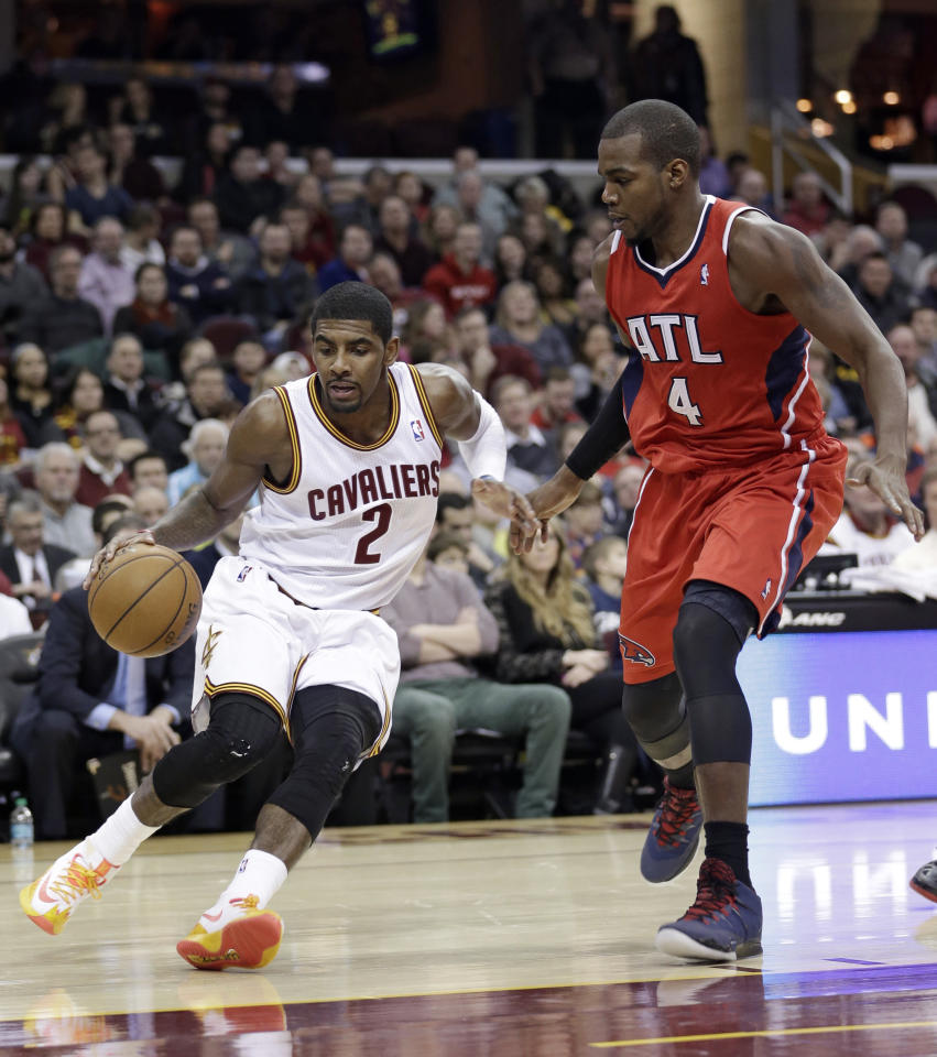 Cleveland Cavaliers' Kyrie Irving (2) drives past Atlanta Hawks' Paul Millsap (4) during the first quarter of an NBA basketball game Thursday, Dec. 26, 2013, in Cleveland. (AP Photo/Tony Dejak)