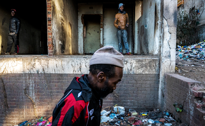 An unknown man walks past two others at the entrance to the derelict San Jose building in Johannesburg, South Africa