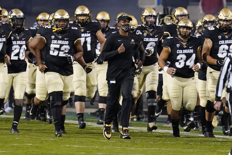 FILE - In this Nov. 7, 2020, file photo, Colorado head coach Karl Dorrell, center, leads his players onto the gridiron to host UCLA in an NCAA college football game in Boulder, Colo. Dorrell was selected as the PAC-12 coach of the year. (AP Photo/David Zalubowski, File)