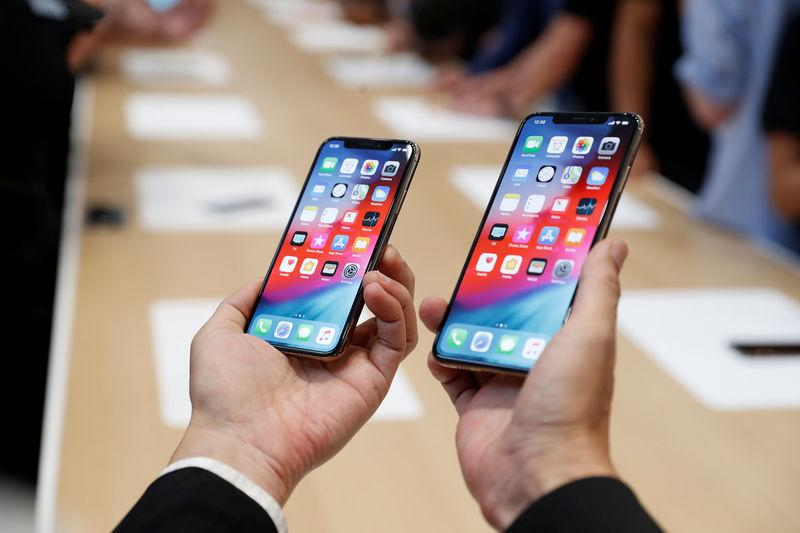 FILE PHOTO: A man holds the newly released Apple iPhone XS and XS Max during a product demonstration following the Apple launch event at the Steve Jobs Theater in Cupertino, California, U.S. September 12, 2018. REUTERS/Stephen Lam/File Photo