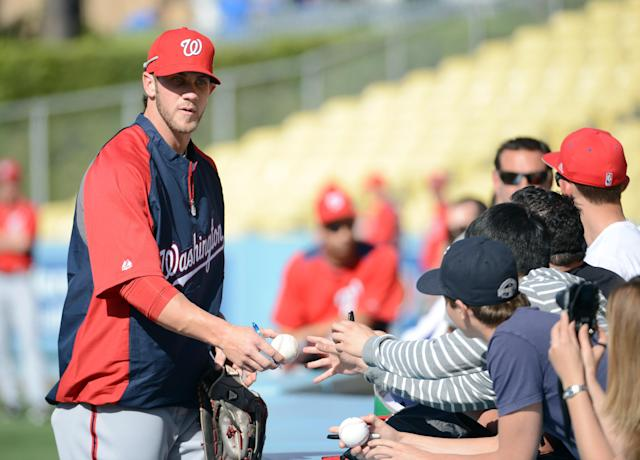 LOS ANGELES, CA - APRIL 28: Bryce Harper #34 of the Washington Nationals sings autographs as he makes his major league debut during practice before the game against the Los Angeles Dodgers at Dodger Stadium on April 28, 2012 in Los Angeles, California. (Photo by Harry How/Getty Images)