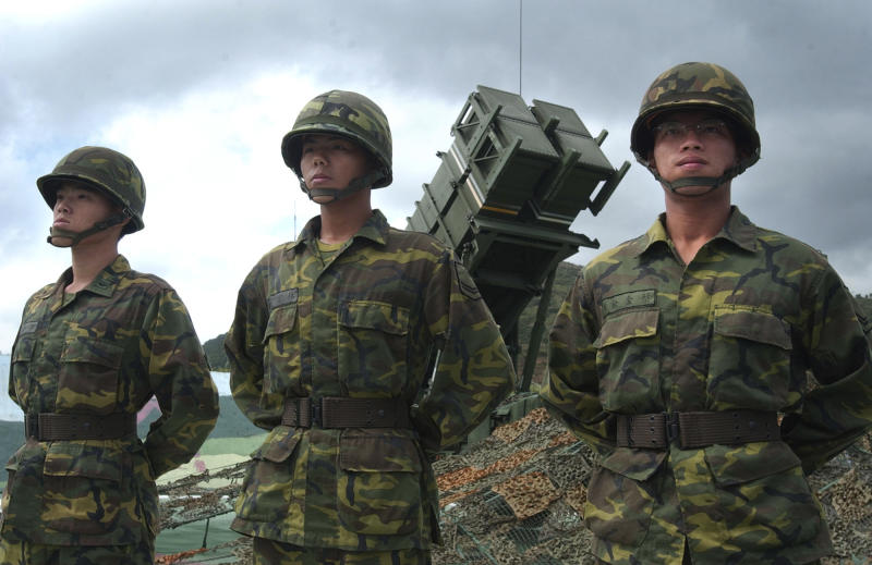 In this Oct. 22, 2004 photo, Taiwanese soldiers stand in attention in front of a Patriot missile air defense system near the northern coastal town of Wanli, Taiwan. With the fourth Taiwanese in only 14 months known to have been picked up by authorities on charges of spying for China, it appears that the rival mainland is aggressively targeting high-tech US-made defense systems on the island.  (AP Photo/Wally Santana)