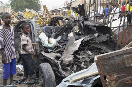 Two boys stand near charred chassis of vehicle after bomb attack near busy market area in Ajilari-Gomari near city's airport, in Maiduguri