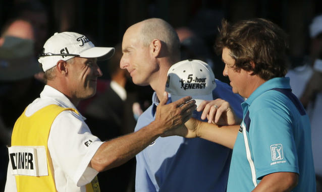Jason Dufner, right, celebrates winning the PGA Championship golf tournament with his caddie Kevin Baile as Jim Furyk, center, walks past at Oak Hill Country Club, Sunday, Aug. 11, 2013, in Pittsford, N.Y. (AP Photo/Charlie Riedel)