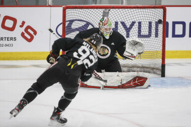 Chicago Blackhawks goaltender Collin Delia defends against left wing Alex Nylander during NHL hockey practice at Fifth Third Arena on Monday, July 13, 2020, in Chicago. (AP Photo/Kamil Krzaczynski)