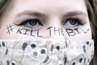 """A demonstrator wears a face mask and a slogan painted on her face during a """"Kill the Bill"""" protest in London, Saturday, April 3, 2021. The contentious Police, Crime, Sentencing and Courts Bill going through Parliament would give police stronger powers to restrict protests. (AP Photo/Alberto Pezzali)"""