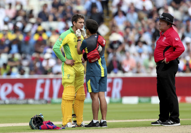 Australia's Alex Carey, left, is attended by a medic after he was hit off the bowling of England's Jofra Archer during the Cricket World Cup semi-final match between England and Australia at Edgbaston in Birmingham, England, Thursday, July 11, 2019. (AP Photo/Aijaz Rahi)