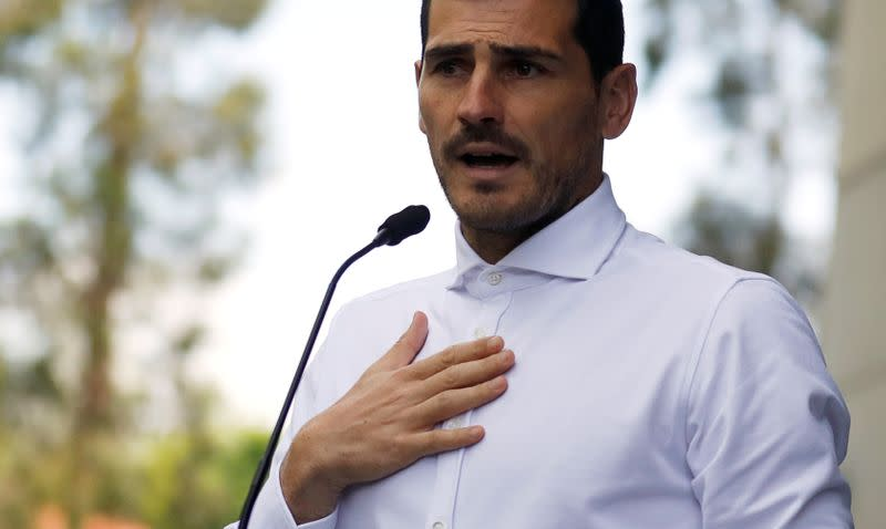 FILE PHOTO: Spanish soccer player Iker Casillas speaks to journalists before he leaves CUF Porto hospital accompanied by his wife Sara Carbonero in Porto