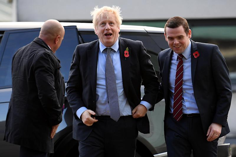 ELGIN, SCOTLAND - NOVEMBER 07: Prime Minister Boris Johnson (C) is greeted by Conservative party candidate for Moray, Douglas Ross (R) as he arrives for a general election campaign visit to Diageo's Roseisle Distillery on November 07, 2019 near Elgin in Scotland, United Kingdom. (Photo by Daniel Leal-Olivas - WPA Pool/Getty Images)