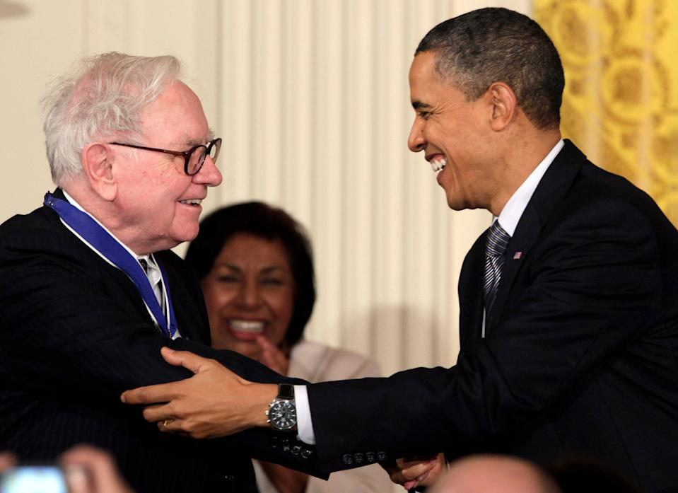 """FILE - In this Feb. 15, 2010, file photo President Barack Obama congratulates Warren Buffett after presenting him with a 2010 Presidential Medal of Freedom in an East Room ceremony at the White House in Washington. In his weekly radio and internet address Saturday April 14, 2012, Obama urged Americans to ask their member of Congress to support the """"Buffett Rule,"""" named after the billionaire investor who says he pays a lower tax rate than his secretary. Obama says the nation can't afford to keep giving tax cuts to the wealthiest, """"who don't need them and didn't even ask for them."""" (AP Photo/Carolyn Kaster)"""