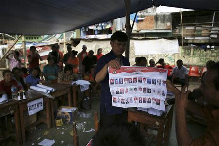 Electoral officials check ballot papers during vote counting at a polling station in Jakarta