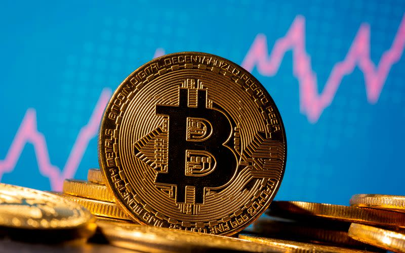 FILE PHOTO: A representation of virtual currency Bitcoin is seen in front of a stock graph